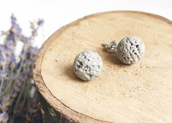 two light grey spherical stud earrings laying on wood disk with dried lavender in the background