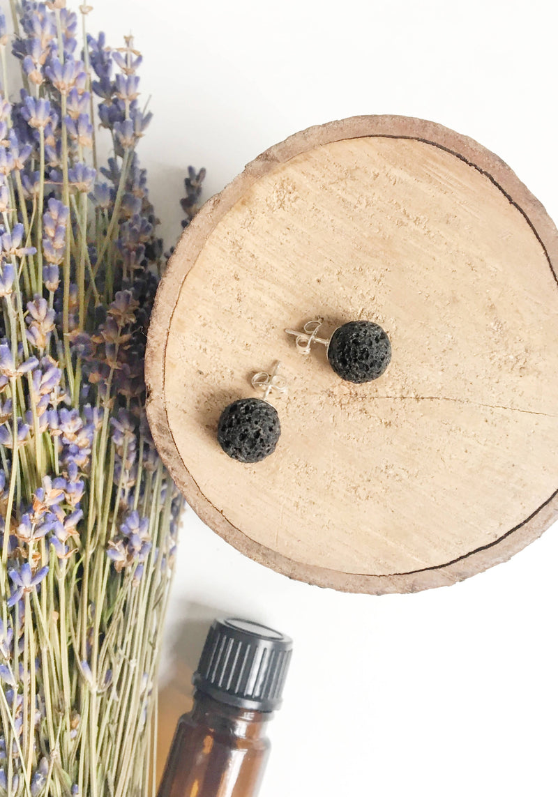 aerial view of two black spherical stud earrings laying on wood disk with dried lavender in the background and a brown essential oil bottle laying on it's side
