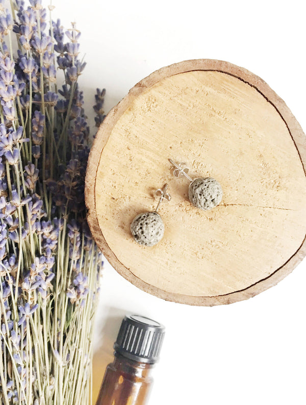 aerial view of two light grey spherical stud earrings laying on wood disk with dried lavender and a brown essential oil bottle laying on it's side in the background
