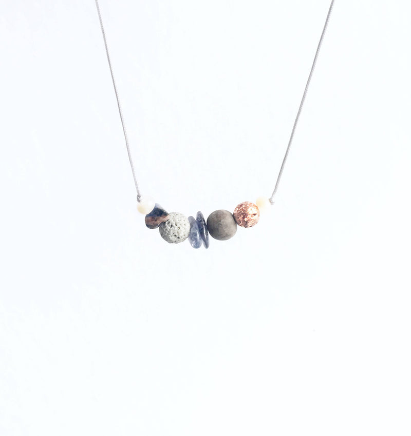 cropped photo of necklace hanging in v-shape, showing different colours of stones (grey, blue, light pink), with grey cord