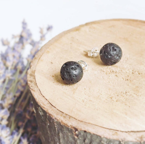 two black spherical stud earrings laying on wood disk with dried lavender in the backgroun
