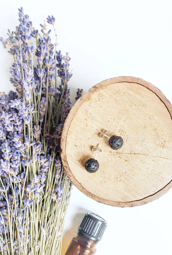 aerial view of two black spherical stud earrings laying on wood disk with dried lavender and a brown essential oil bottle in the backgroun