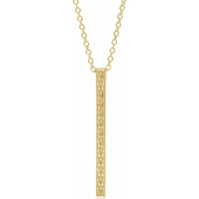 Close up of yellow gold detailed bar necklace