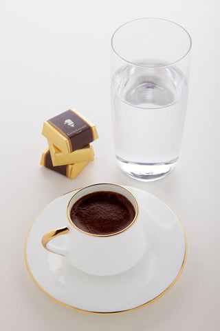 Turkish coffee cup and saucer with water and dessert