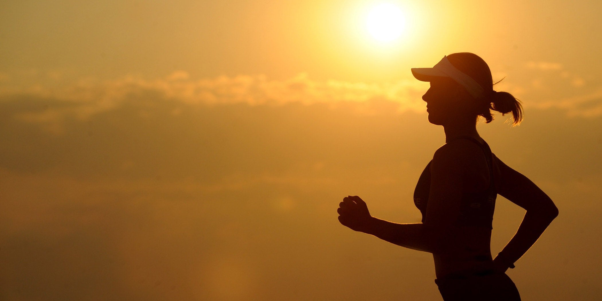 fit woman running at sunset in shape wearing a hat