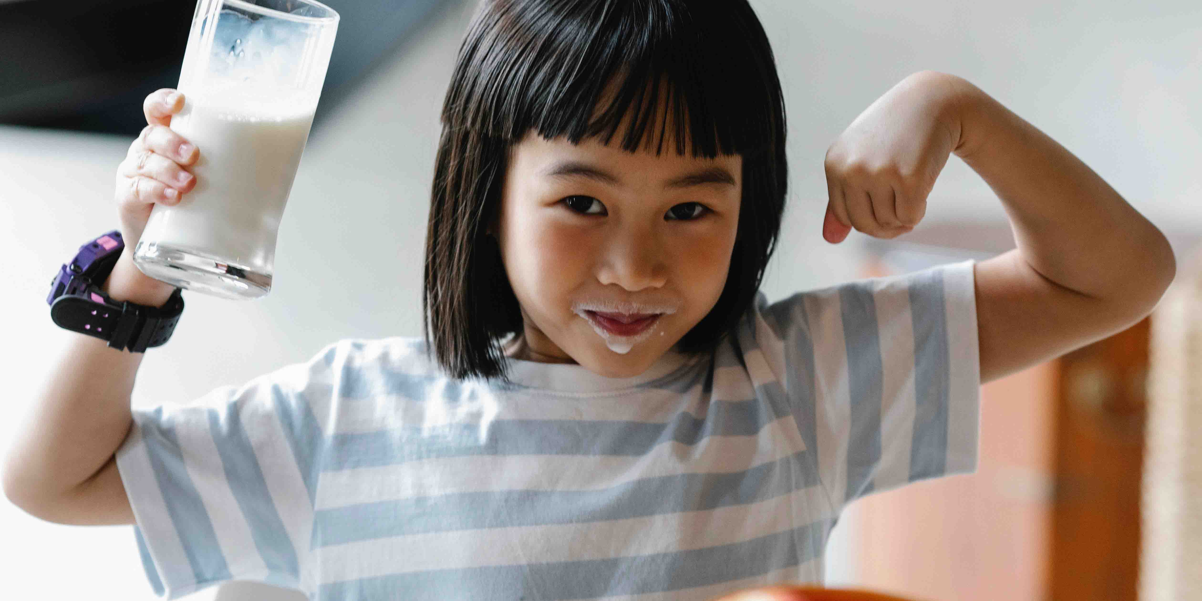 Young child happy drinking milk for bone support calcium