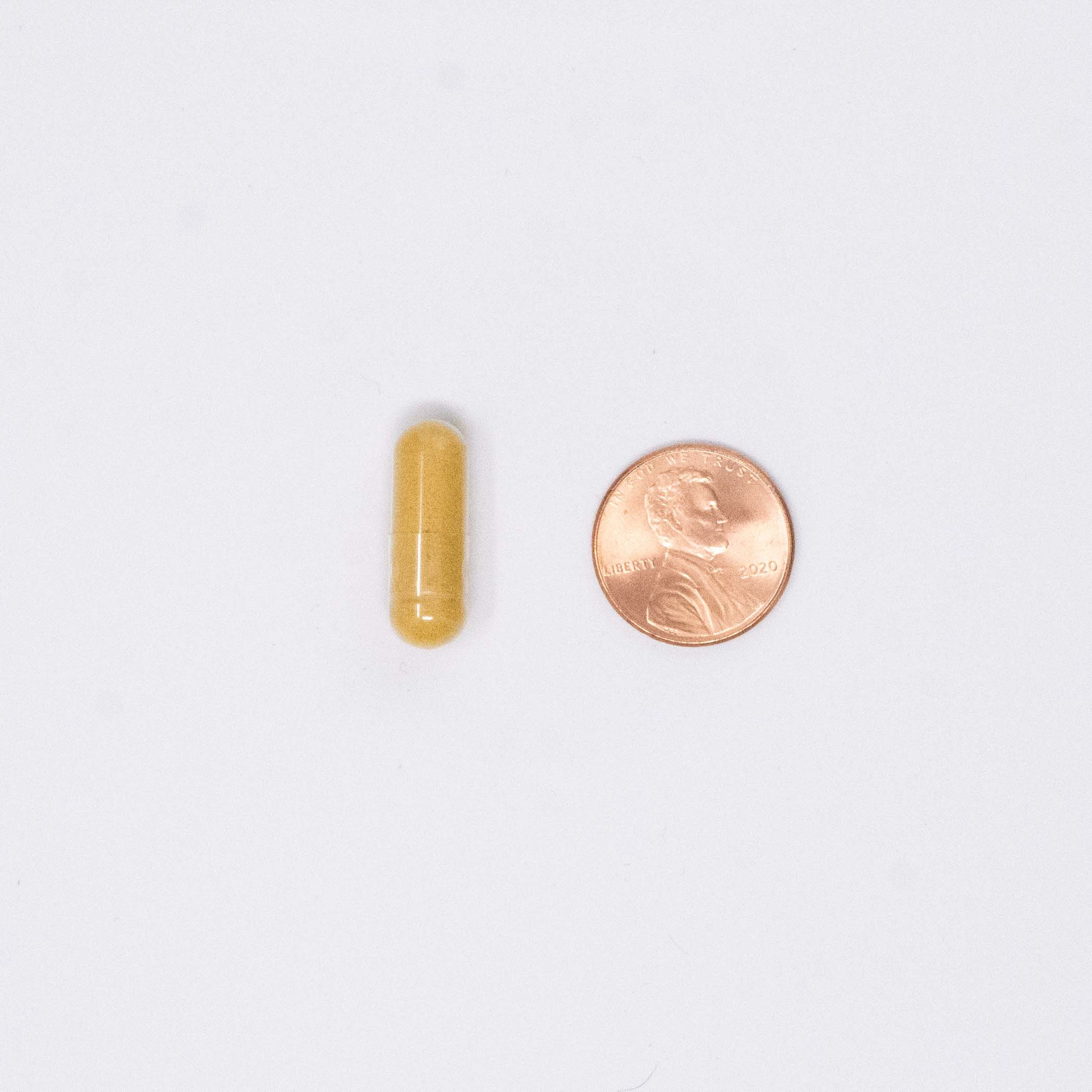 CoQ10 vitamin next to a penny