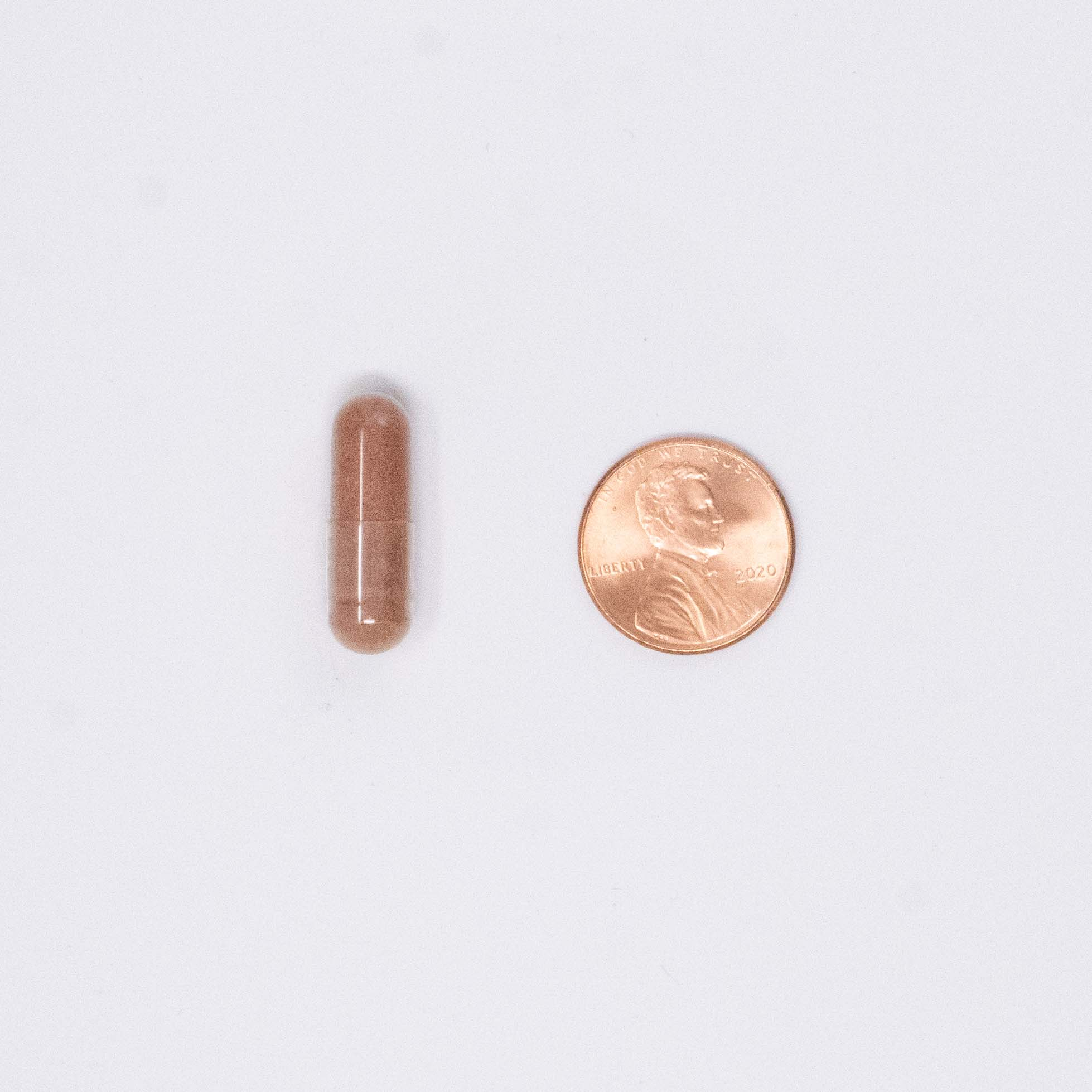 cranberry vitamin next to a penny