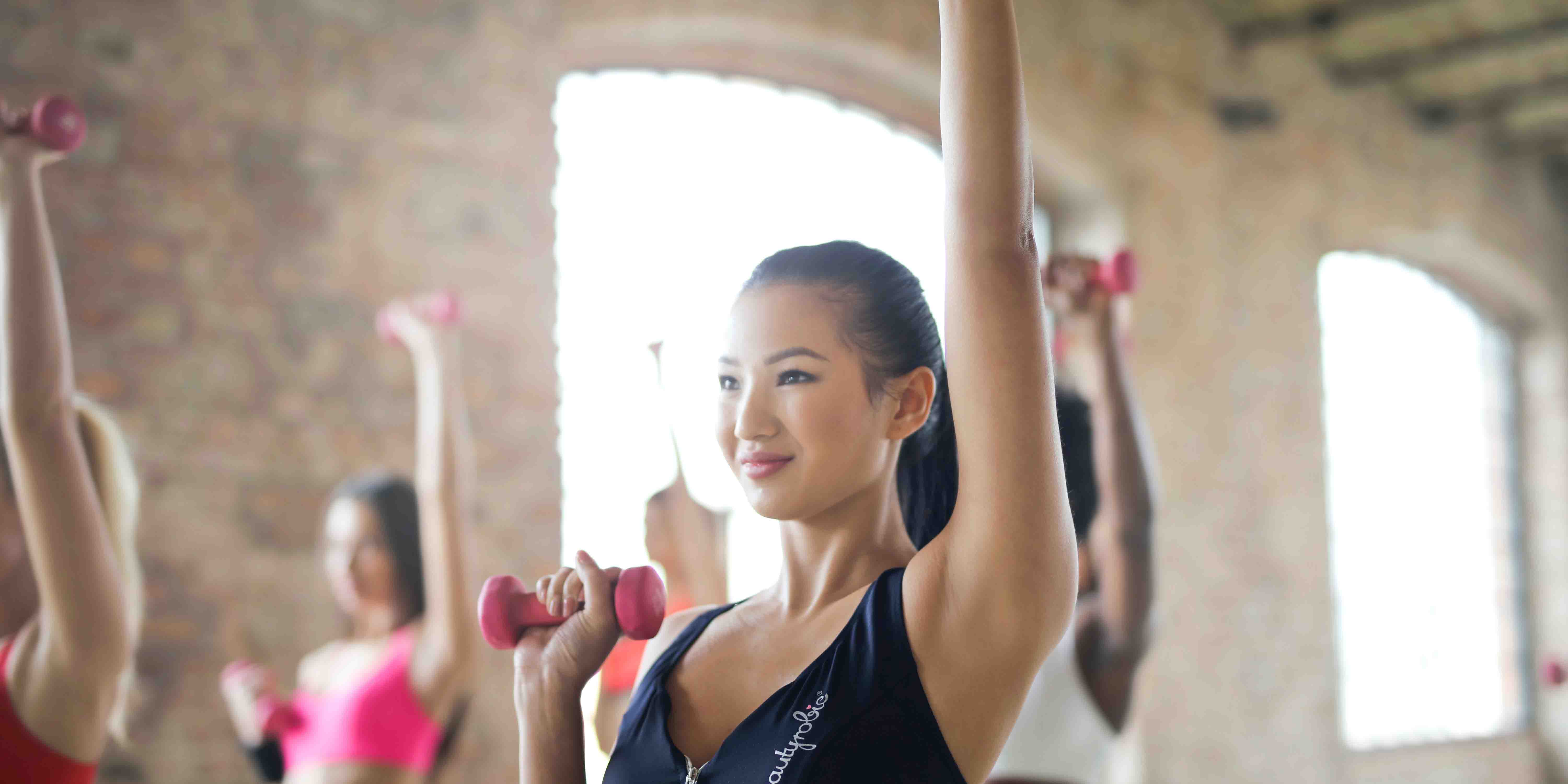 healthy woman exercising with weights taking Ashwagandha promote muscle recovery