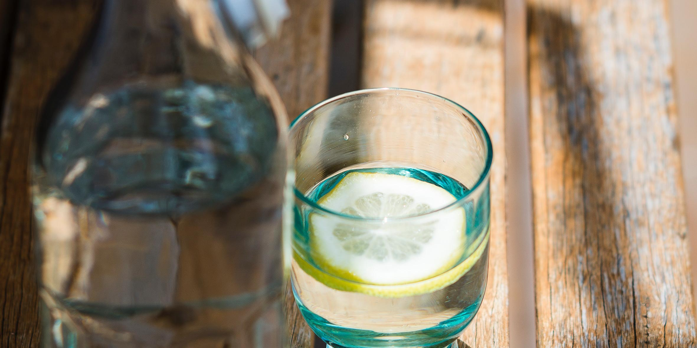 Glass of water with lemon vitamin c on a wooden table