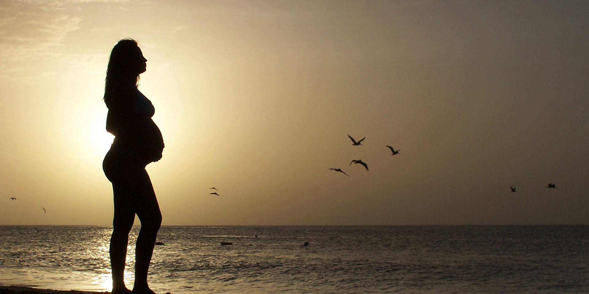 Mother holding her pregnant stomach at the beach taking prenatal vitamins during sunset