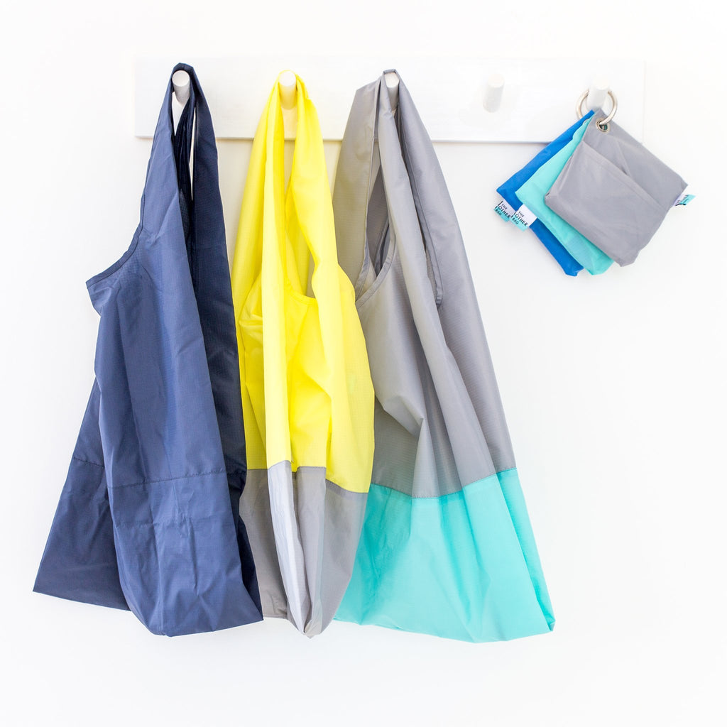 Various recycled foldable tote bags hanging