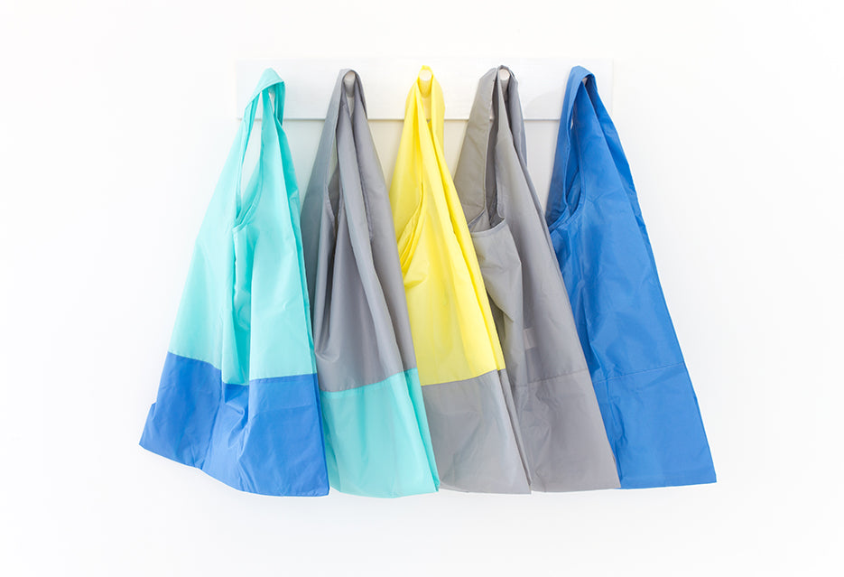 Collection of recycled foldable tote bags in a row