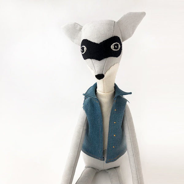 handmade heirloom cloth doll, racoon doll wearing a jean jacket vest.