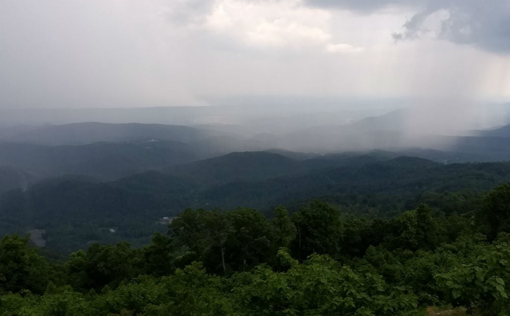 View from Windrock overlook in Tennessee, showing green hills and valleys, and a gentle rain shower in the distance.