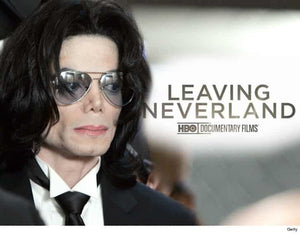 Michael Jackson, in a black suit, white shirt, black tie and faded sheer black aviator glasses.  Leaving Neverland HBO