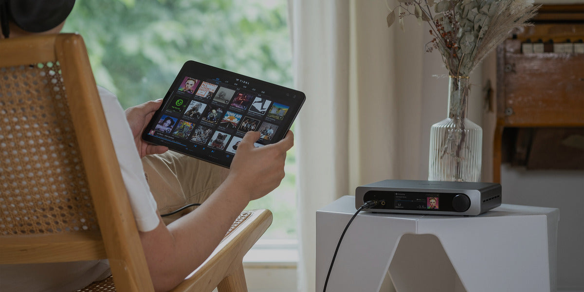 Woman on a chair holding tablet to stream music using Matrix mini-i pro 3