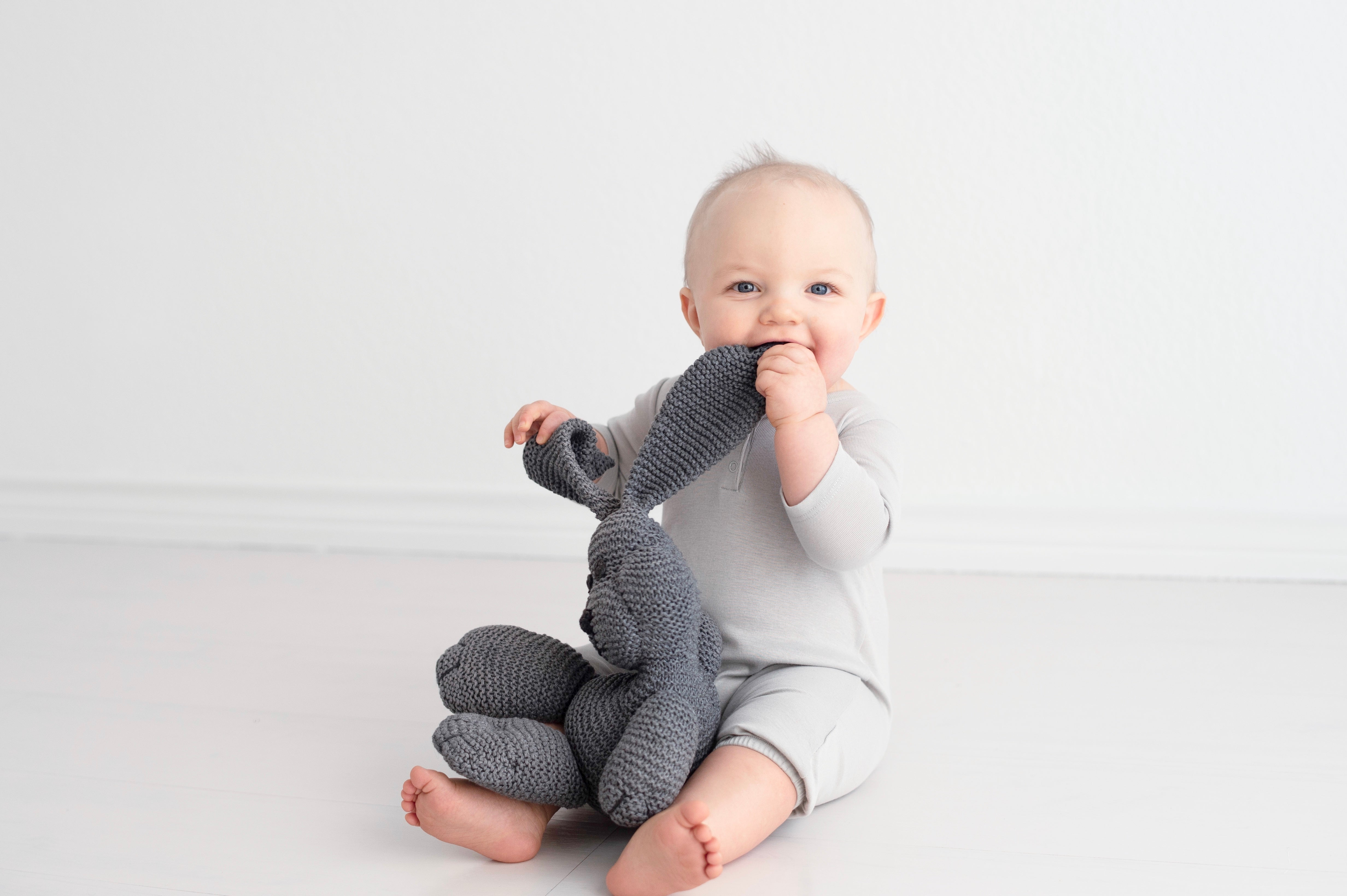 Cool grey long sleeved henley balloon coverall with charcoal color hand knit snuggle bunny organic soft toy