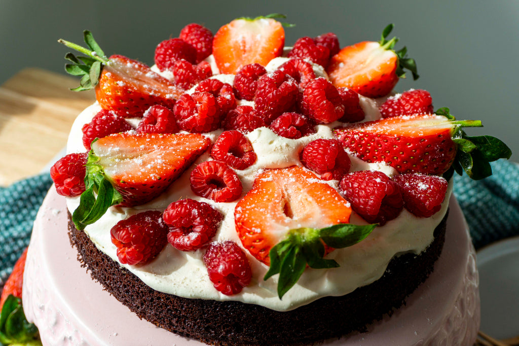 Birds eye view of low carb chocolate cake with freshly whipped cream and berries served on top
