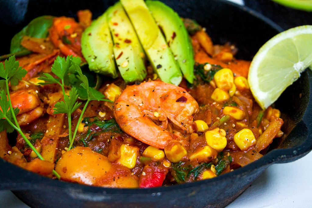 Side shot of Mexican style prawns in a skillet served with avocado and a wedge of lemon