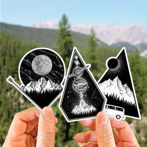 hands holding up a set of three illustrated mountain stickers