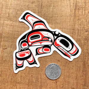 tlingit killer whale laptop vinyl sticker next to a quarter
