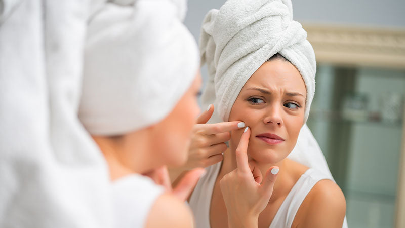 Woman looking at skin in face mirror. benefits of hemp extract oil. hemp seed extract benefits.