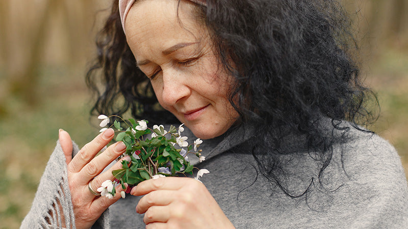 Woman smelling the scent of plants with flowers. What are terpenes in cbd oil? Where to buy cbd oil with terpenes?