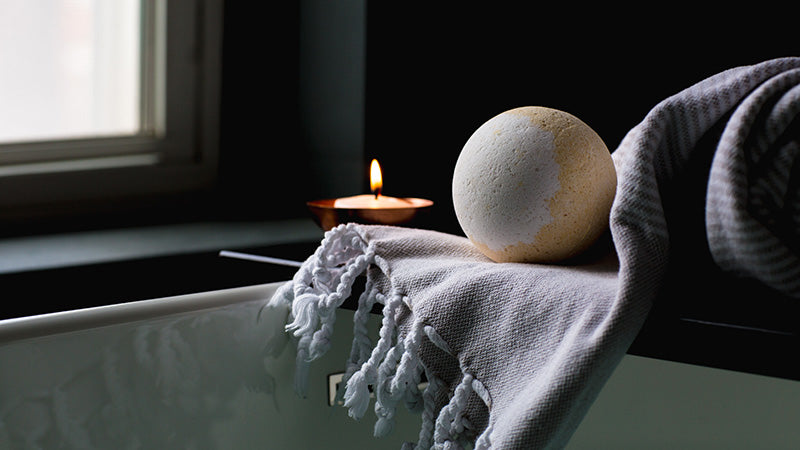 candle burning in relaxing bath setting. cbd oil bath bombs for sale online USA.