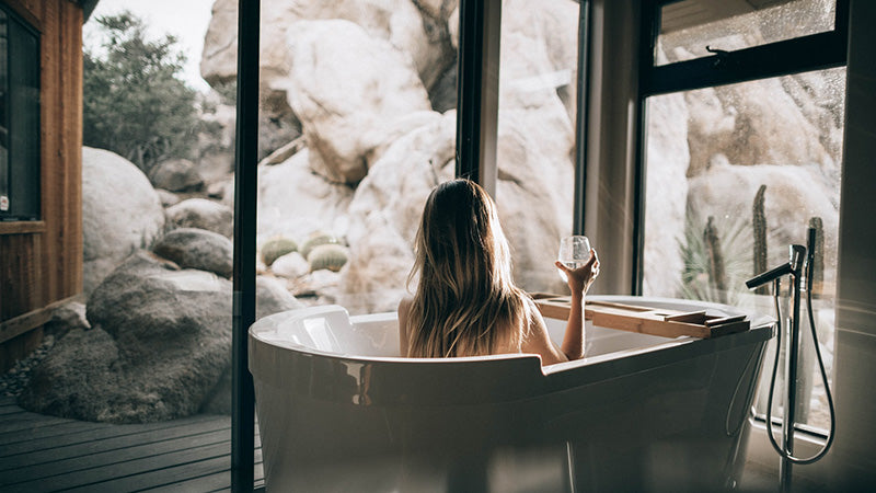 back of woman in bath sipping red wine. cbd beauty products. relaxation in bathtub.