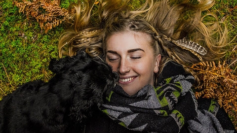 adult woman laying with black dog. is hemp oil safe for dogs?