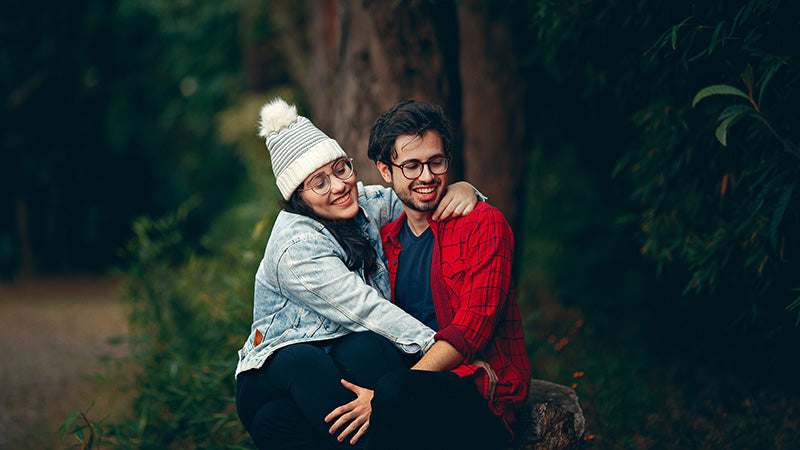 Happy adult couple cuddling in a park. How much cbd oil drops per day for anxiety?