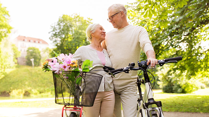 happy elderly couple with their bikes. cbd yoga. yoga and cbd. is cbd oil and yoga good for you? why cbd with yoga is the best idea ever.