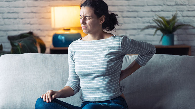 Woman showing signs of a sore lower back. cbd yoga. yoga and cbd. is cbd oil and yoga good for you? why cbd with yoga is the best idea ever.