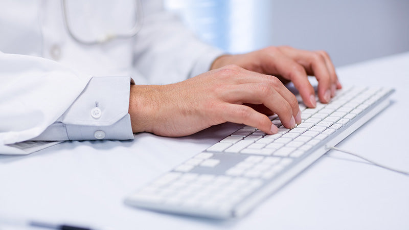 Doctor typing on a keyboard. Is cbd oil safe? How safe is cbd oil? Is cbd oil safe for heart patients? Is it safe to take cbd oil while breastfeeding?