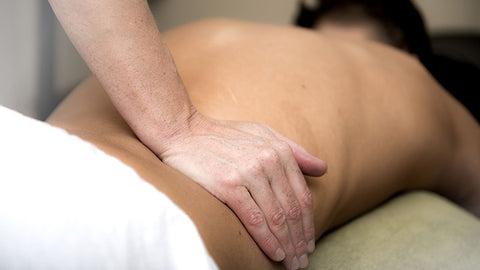 man getting a lower back massage. hemp oil pain relief.