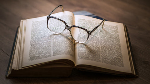 Open book with eye glasses on pages. Buy hemp oil with no THC online USA.