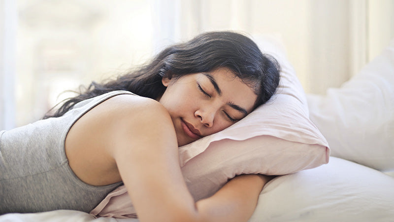 sleeping adult woman after using hemp tincture as a sleep aid for insomnia.