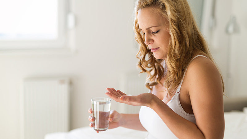 Woman with glass of water ready to take hemp seed oil capsules. buy hemp bomb cbd capsules online.
