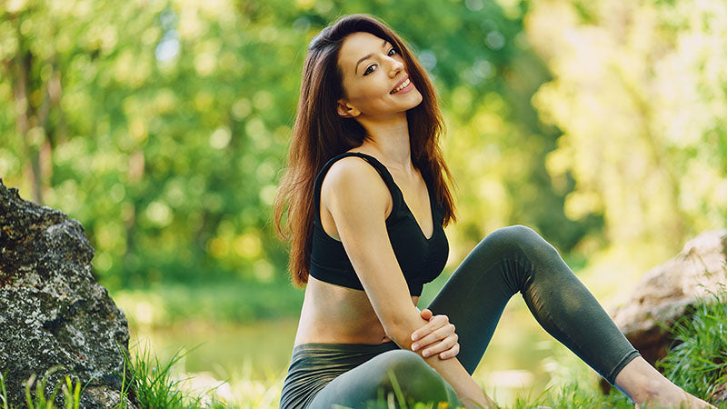 Adult woman smiling in yoga pose in park. cbd and yoga. benefit of cbd yoga. cbd yoga sequence. yoga cbd.