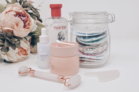 Jar of cotton rounds next to skincare products