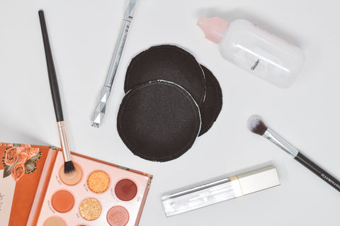 Black reusable cotton rounds surrounded by makeup, makeup brushes, and makeup remover
