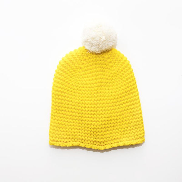 yellow chunky knit beanie hat with white pom pom
