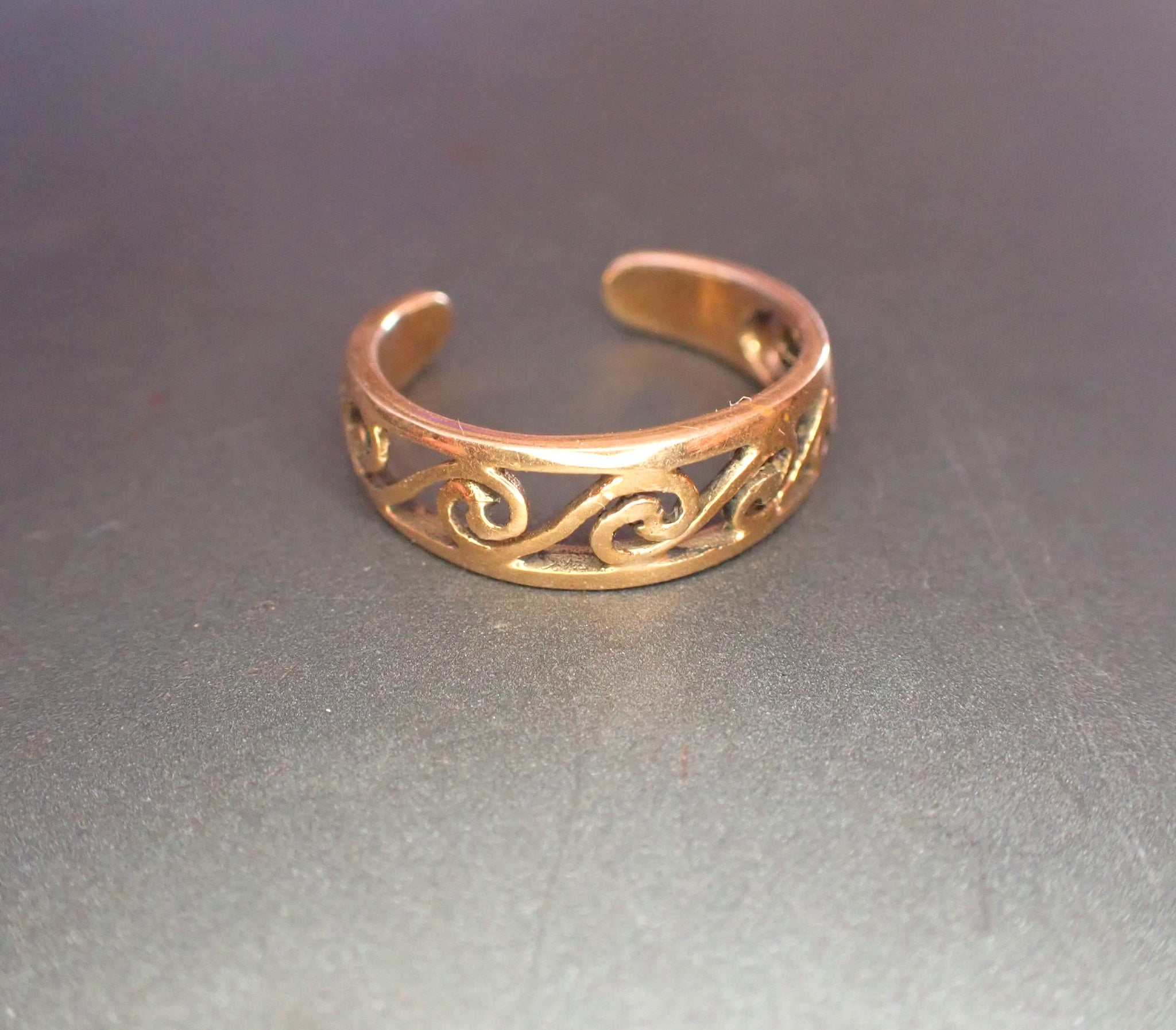 Gold coloured toe ring with swirls