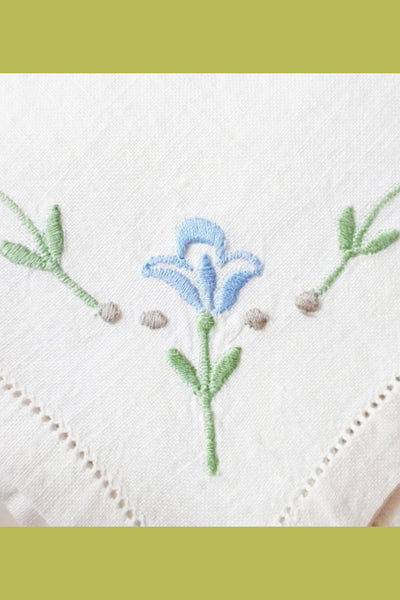 Blue and green embroidered flower on vintage napkin
