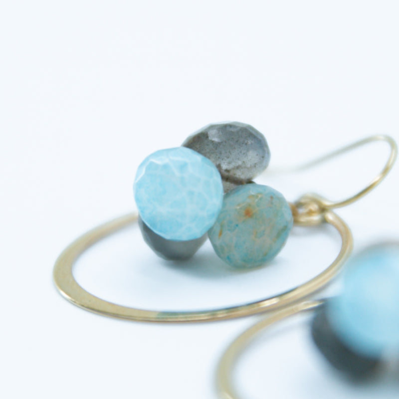 Earring with stones and flattened circle.