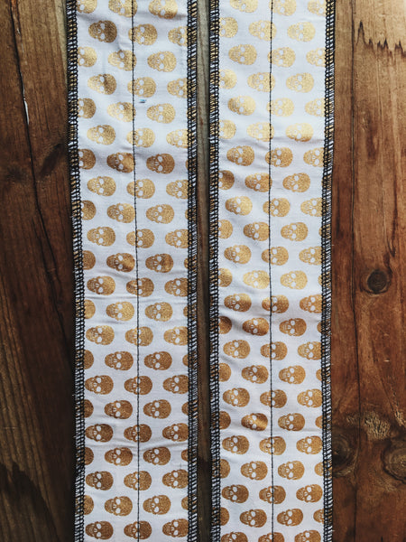 Gold on white skulls wrist wrap