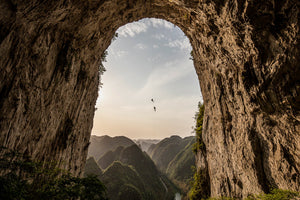 Climbers rappelling from the Getu Arch, China
