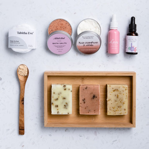 natural, vegan and plastic free skincare products laid out on white background.