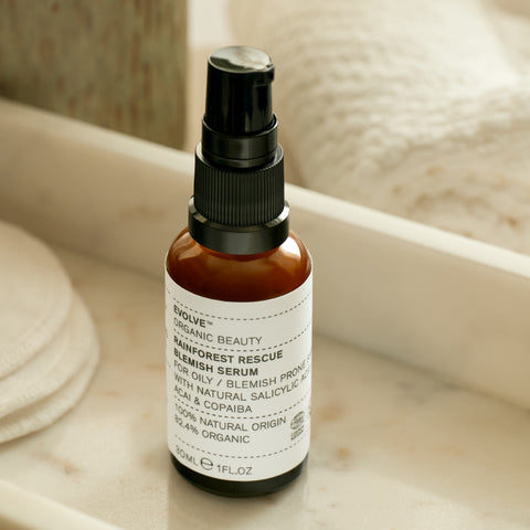 evolve beauty lifestyle image of rainforest rescue blemish serum in amber glass bottle.